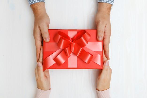 Close up da mão de um homem que dá uma caixa vermelha com um presente a uma mulher.