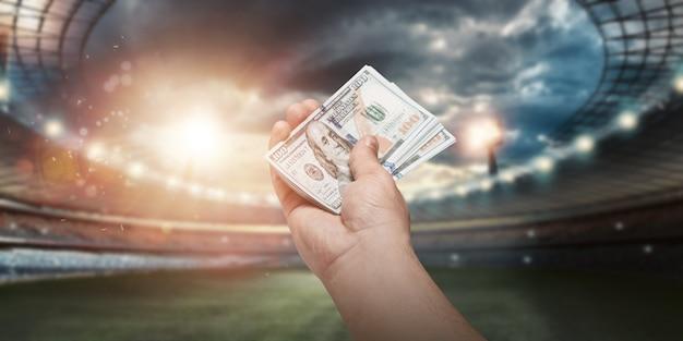Close-up da mão de um homem segurando dólares americanos no contexto do estádio. o conceito de apostas desportivas, lucrar com apostas, jogos de azar. futebol americano.