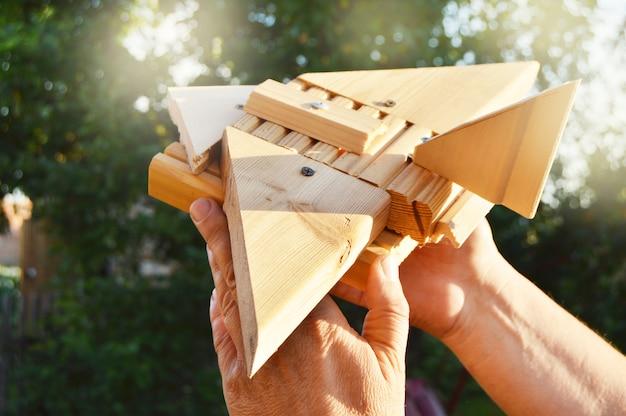 Close-up da mão de um homem segurando um avião caseiro de brinquedo de madeira