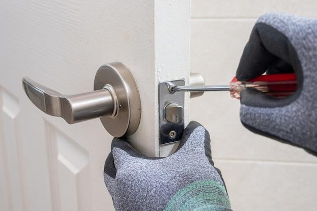 Close-up da mão de um homem segurando uma chave de fenda na mão e fazendo reparos.