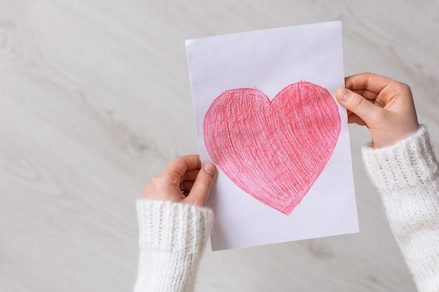 Close-up da mão de uma criança com um coração vermelho desenhado em papel branco sobre um fundo de madeira. dia das mães. o amor da criança por sua mãe. copie o espaço para o texto.