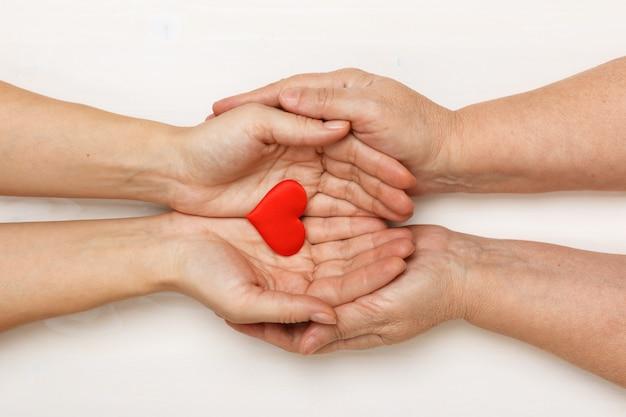 Close-up da mão de uma filha adulta e uma mãe mais velha, segurando um coração juntos