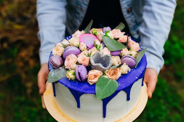 Close-up da mão de uma garota que segurando um bolo e um bolo com um belo design e ornamentos