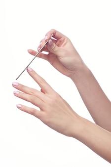 Close up da mão de uma jovem mulher lixando as unhas, sobre fundo branco.