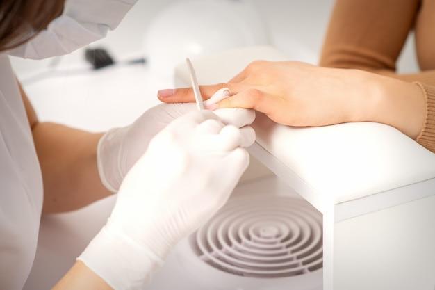 Close-up da mão de uma jovem recebendo o procedimento de lixa de unha em um salão de beleza