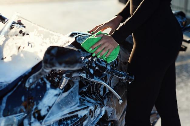 Close-up da mão de uma jovem sedutora lavando a motocicleta esportiva elegante e limpando-a do rosa