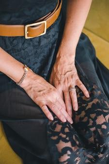 Close-up da mão de uma mulher adulta que encontra-se em seus joelhos em um fundo borrado de um sofá amarelo.