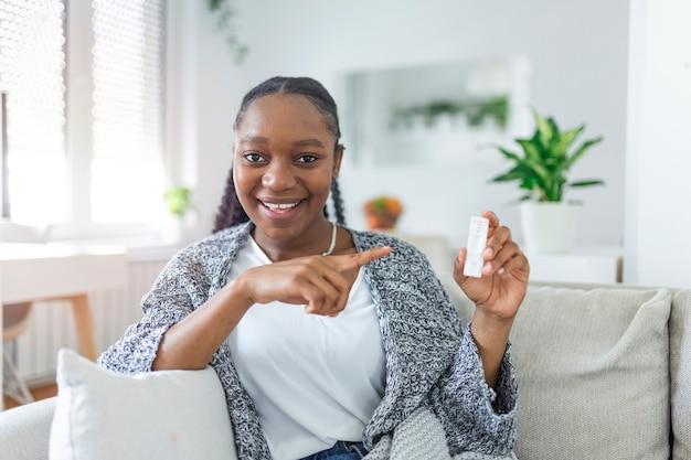 Close-up da mão de uma mulher afro-americana segurando um dispositivo de teste negativo. mulher jovem feliz mostrando seu teste rápido para o coronavírus - covid-19 negativo. o foco está no teste. coronavírus