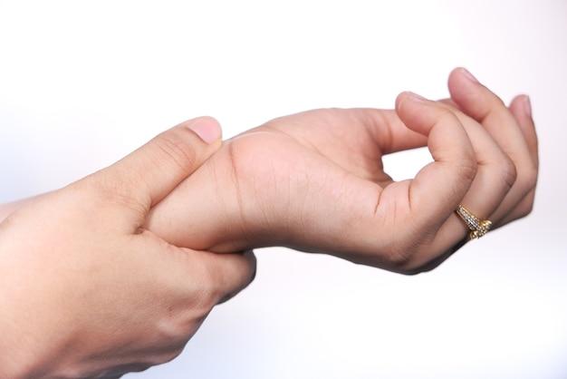Close-up da mão de uma mulher com dor no pulso isolada no branco,
