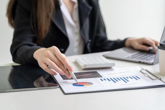 Close-up da mão de uma mulher de negócios segurando uma caneta apontando para uma análise estatística de gráfico, sentado no escritório.