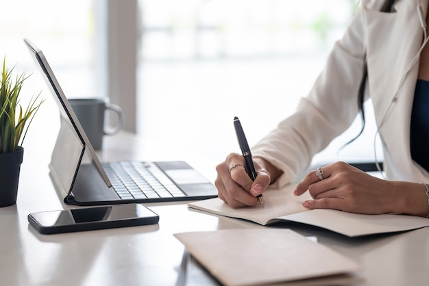 Close-up da mão de uma mulher de negócios segurando uma caneta, tomando notas com o tablet e smartphone no escritório.