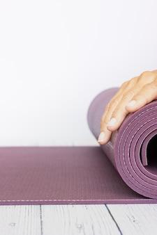 Close-up da mão de uma mulher, desdobrando um tapete de ioga violeta na superfície de madeira branca
