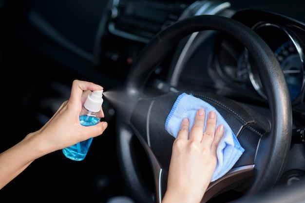 Close-up da mão de uma mulher está limpando o carro com spray de álcool