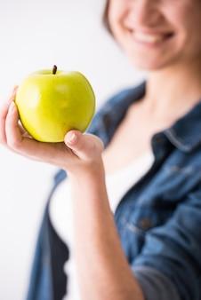 Close-up da mão de uma mulher está segurando a maçã.