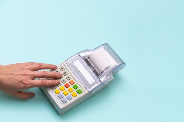 Close-up da mão de uma mulher, pressionando os botões da caixa registradora, sobre fundo azul, vista superior, copie o espaço. conceito de negócios, comércio e compras