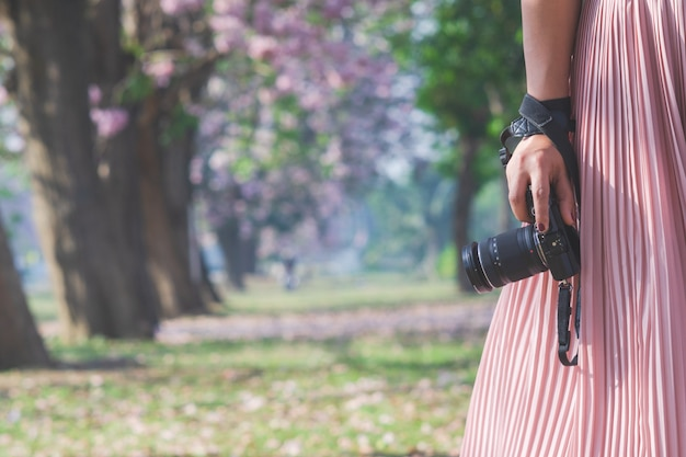 Close-up da mão de uma mulher segurando a câmera.