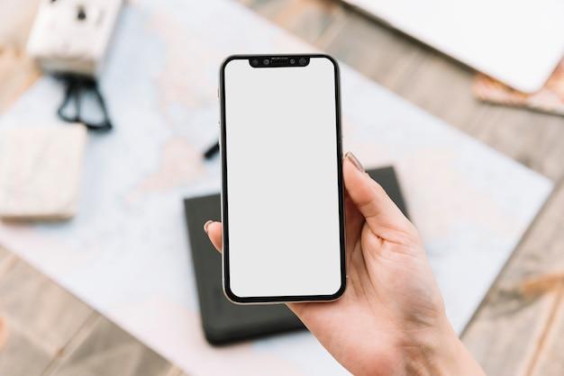 Close-up da mão de uma mulher segurando o telefone inteligente com tela em branco