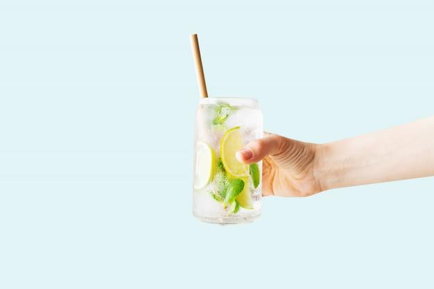 Close up da mão de uma mulher segurando um copo de cocktail tropical mojito