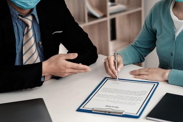 Close-up da mão de uma mulher segurando uma caneta, assinando um currículo para trabalharem juntos no escritório.