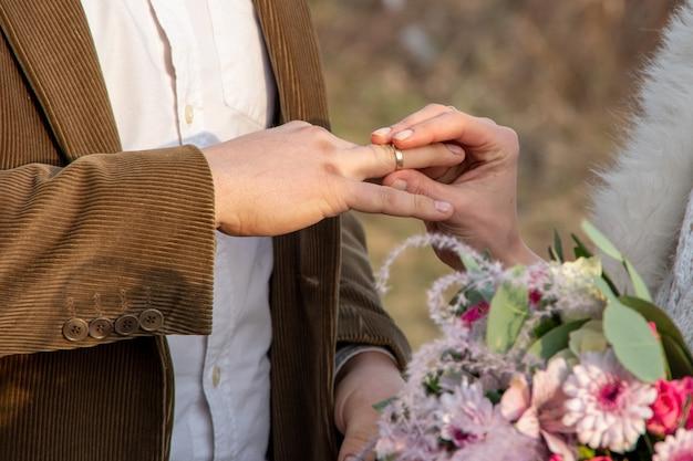 Close-up da mão de uma noiva coloca um anel na mão de um homem. registro externo