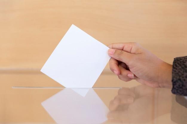 Close-up da mão de uma pessoa inserindo um envelope em branco em uma urna eleitoral