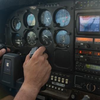 Close up da mão de uma pessoa no painel de controle de um hidroavião, ilhas bay, honduras