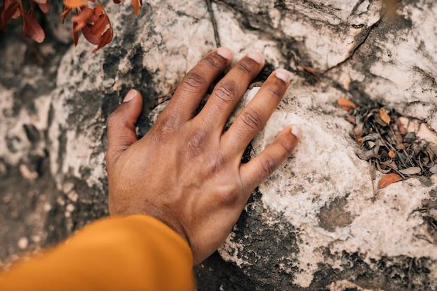 Close-up da mão do caminhante masculino tocando a rocha