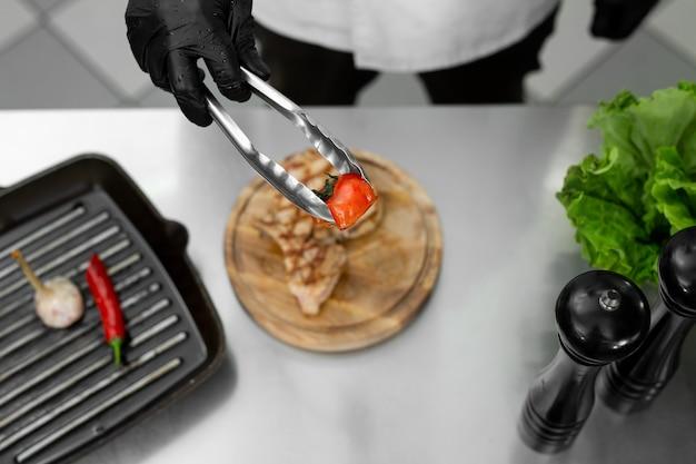 Close-up da mão do chef enquanto ele coloca um tomate da grelha em um prato com pinças
