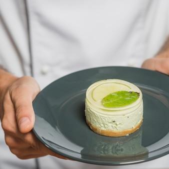 Close-up da mão do chef segurando uma deliciosa sobremesa na placa reflexiva