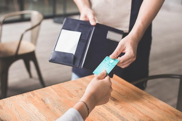 Close-up da mão do cliente pagando suas contas com cartão de crédito