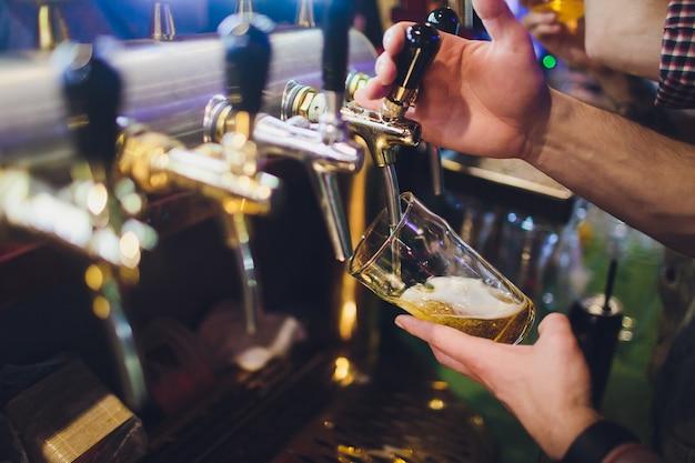 Close-up da mão do empregado de bar na torneira da cerveja, derramando uma cerveja de pressão.