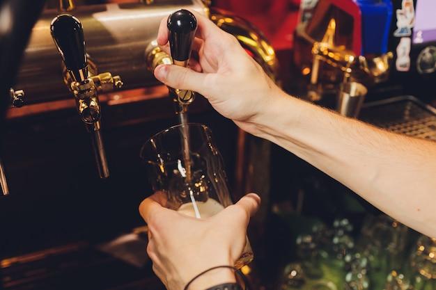 Close-up da mão do empregado de bar na torneira de cerveja, derramando uma cerveja de pressão.