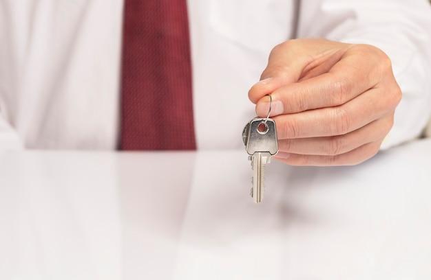 Close-up da mão do empresário na gravata segurando e dando a chave de um novo apartamento, mesa branca com reflexão