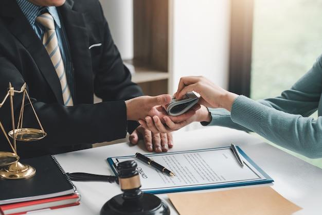 Close-up da mão do empresário recebendo dinheiro de suborno de cliente do sexo feminino, assinando contrato no escritório.