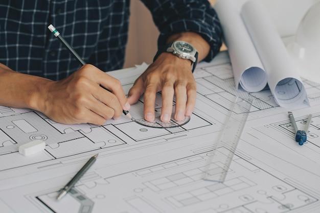 Close up da mão do engenheiro, desenho de plano na impressão azul com equipamento de arquiteto e plano arquitetônico