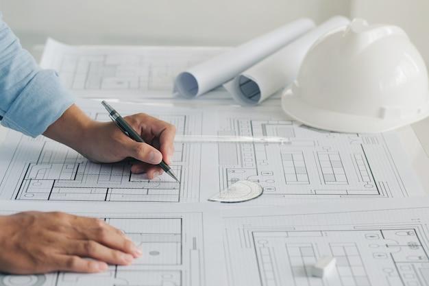 Close-up da mão do engenheiro, desenho de plano na impressão azul com o projeto de arquitetura do equipamento do arquiteto