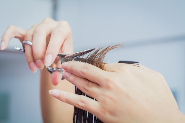 Close-up da mão do esteticista com um corte de cabelo de mulher