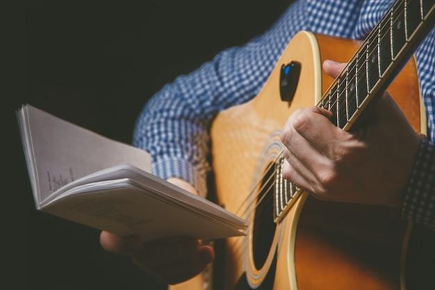Close-up da mão do guitarrista tocando violão
