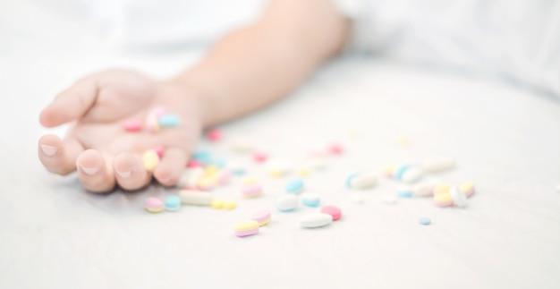Close up da mão do homem com pílulas cometer suicídio por overdose de medicação