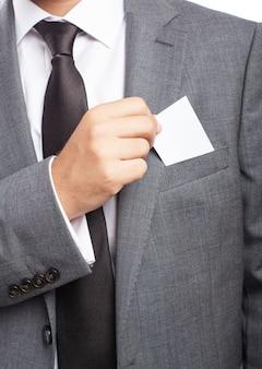 Close-up da mão do homem de negócios que toma um cartão em branco