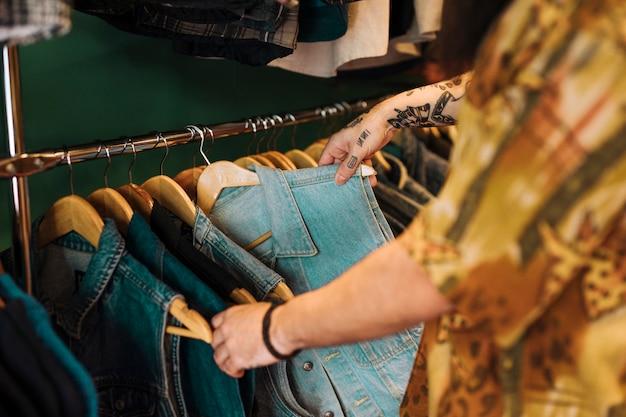 Close-up da mão do homem, escolhendo o casaco azul pendurado no trilho na loja de roupas