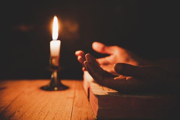 Close-up da mão do homem está rezando na igreja com vela acesa