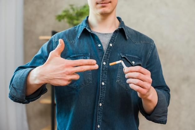 Close-up da mão do homem, mostrando o gesto de arma perto do cigarro quebrado