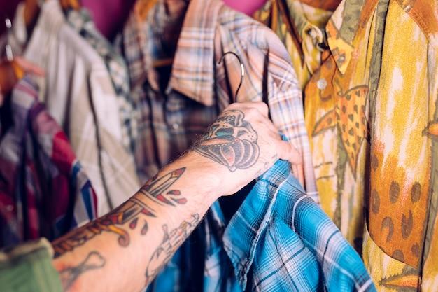 Close-up da mão do homem segurando a camisa azul no trilho na loja de roupas