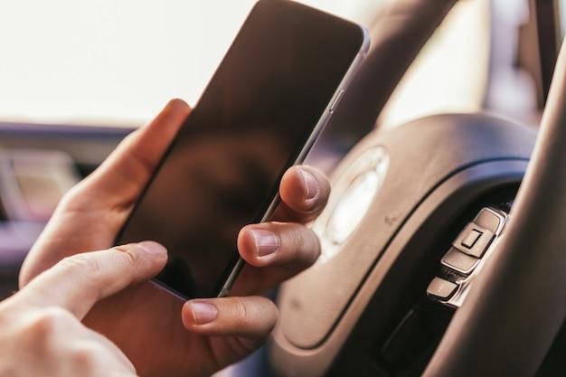 Close-up da mão do jovem com smartphone dirigindo o carro