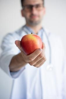 Close-up da mão do médico dando a maçã vermelha. jovem, caucasiano, macho, odontólogo