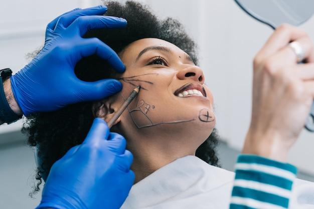Close-up da mão do médico desenhando linhas de correção no rosto de mulher jovem. procedimento antes da cirurgia plástica.