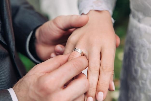 Close-up da mão do noivo coloca um anel de casamento no dedo noivas, a cerimônia na rua, foco seletivo