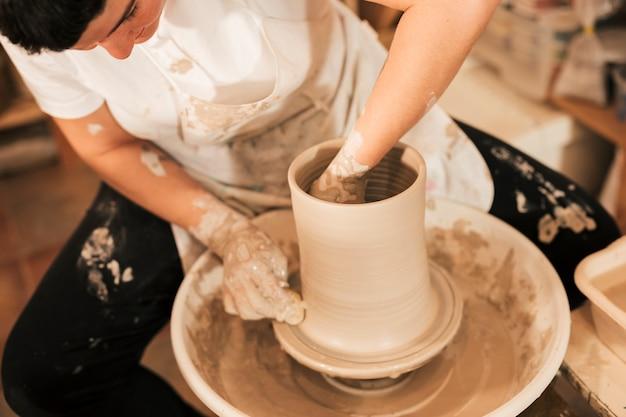 Close-up da mão do oleiro feminino fazendo panela de barro na roda de oleiro