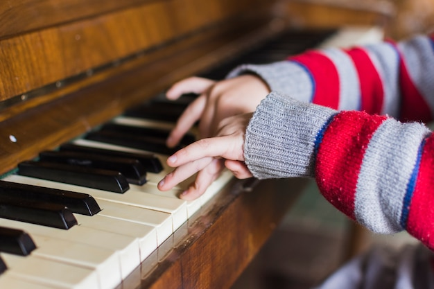Close-up da mão dos meninos, tocando teclas de piano